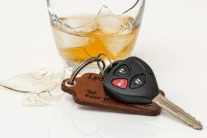 Broken glass of alcohol sitting beside car keys