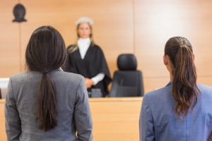 female defendant and her criminal defense attorney standing in front of a judge