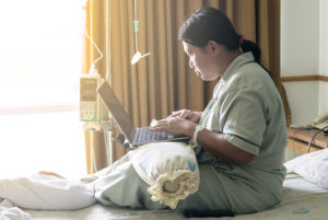woman in hospital looking for personal injury attorney on laptop