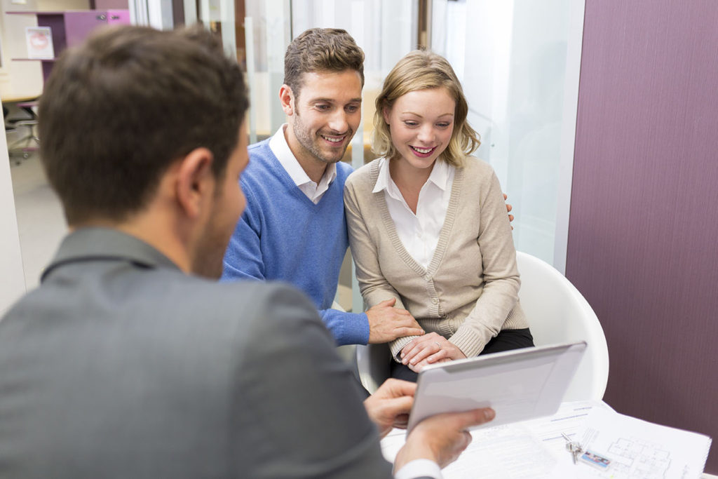 real estate lawyer reviews documents with couple
