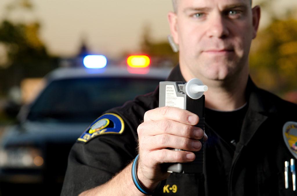cop holding dui dwi breathalyzer